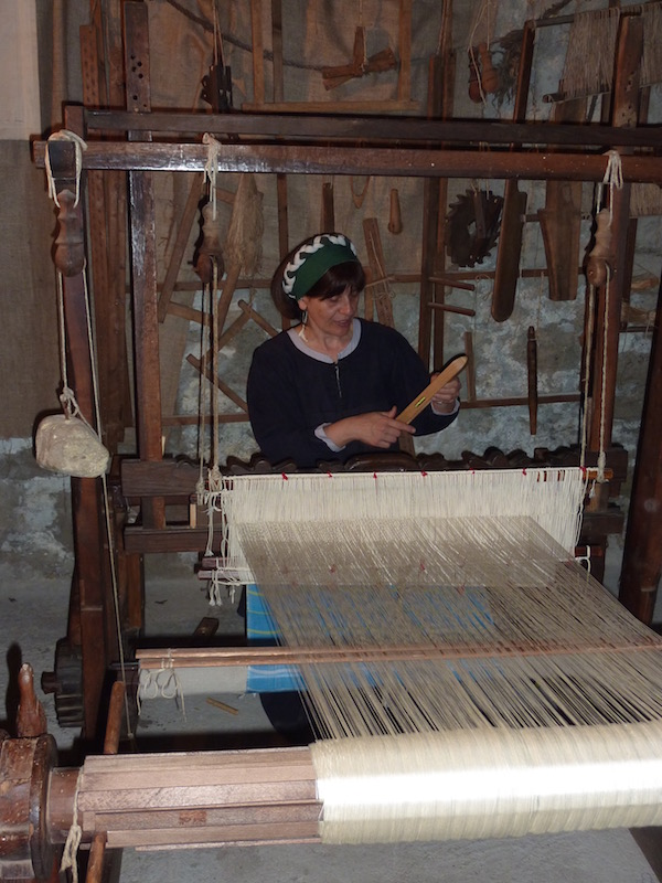 A weaver working on an antique loom